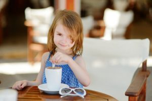 Young girl stirring coffee, demonstrating how children individualize